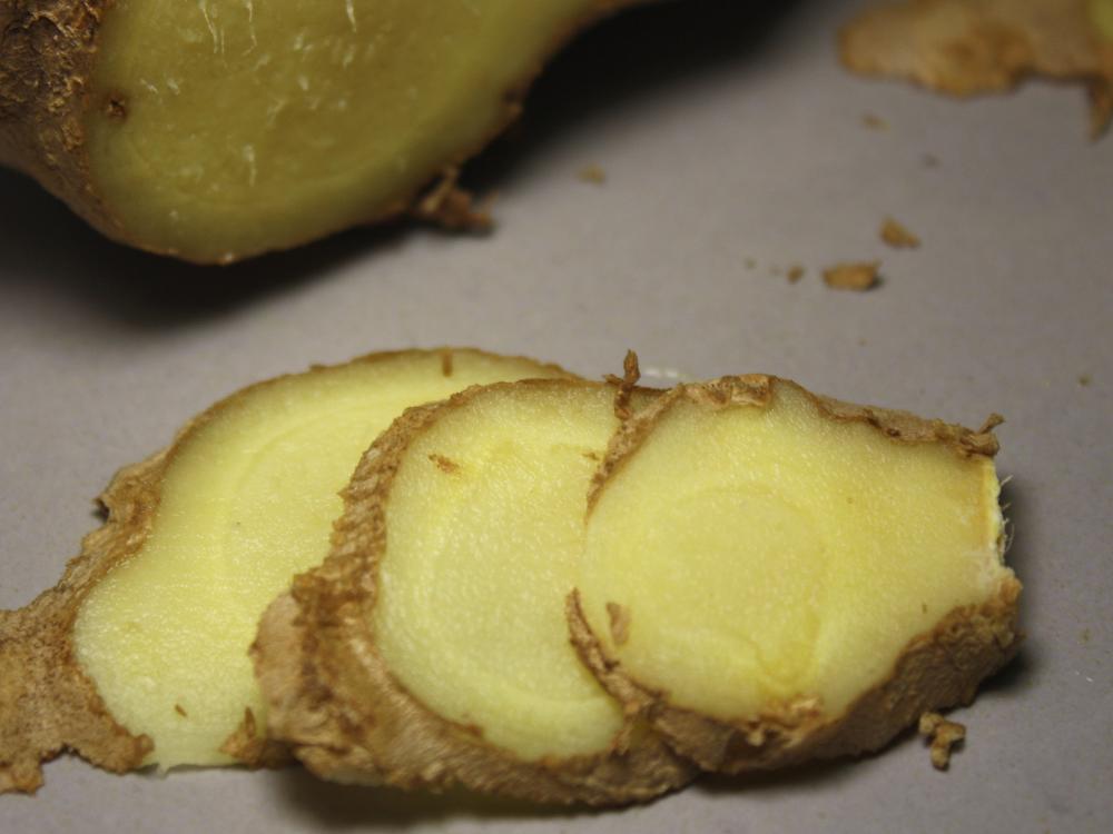 Stück Ingwerrhizom ungeschält und in Scheiben geschnitten